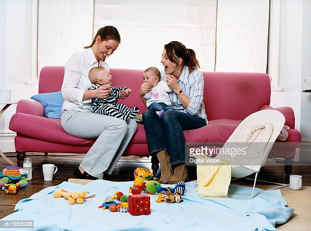 Mothers on a Sofa in a Living Room With Their Babies