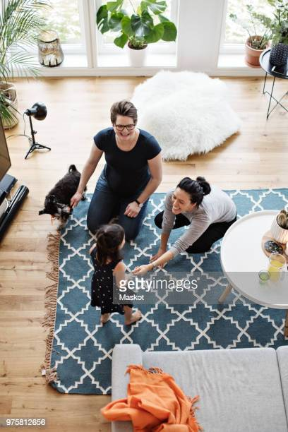 Mothers playing with daughter while sitting by dog in living room at home