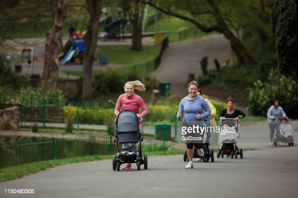 mothers racing with their babies - sprinting stock pictures, royalty-free photos & images