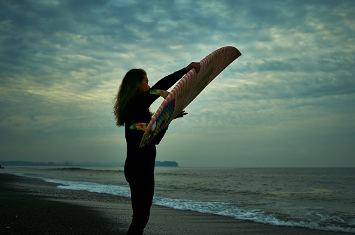 Mother's senior surfer carries board at before sunrise in Enoshima island Japan. - gettyimageskorea