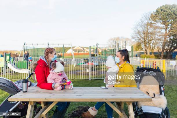 mothers social distancing at the park - flatten the curve stock pictures, royalty-free photos & images