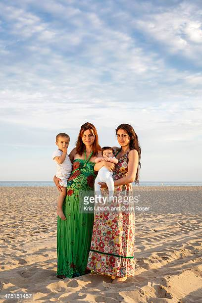 Mothers standing on beach holding baby and toddler