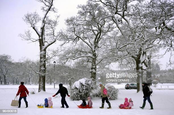Mothers tow children on their sledges across the Village Green on their way to class at Oakwood Infant School in Hartley Wintney in Hampshire 40...