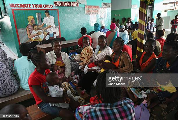 Mothers wait for their children to receive routine vaccinations at Redemption Hospital formerly an Ebola holding center on February 2 2015 in...