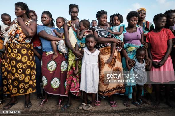 Mothers wait with their children following a line on a ground to receive food distribution from a local supermarket at an evacuation center in Dondo...