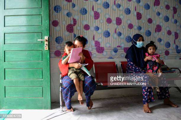 Mothers wait with their children to be administered the polio and Bacillus CalmetteGuerin vaccines at an integrated services post in Banda Aceh on...