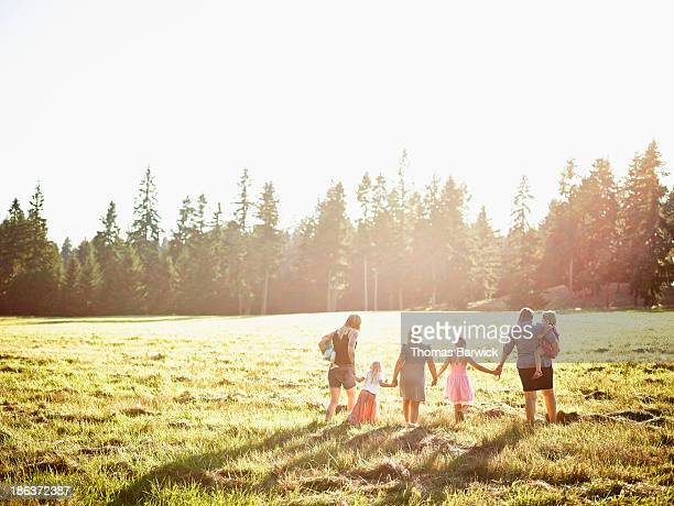 Mothers walking through field with daughters