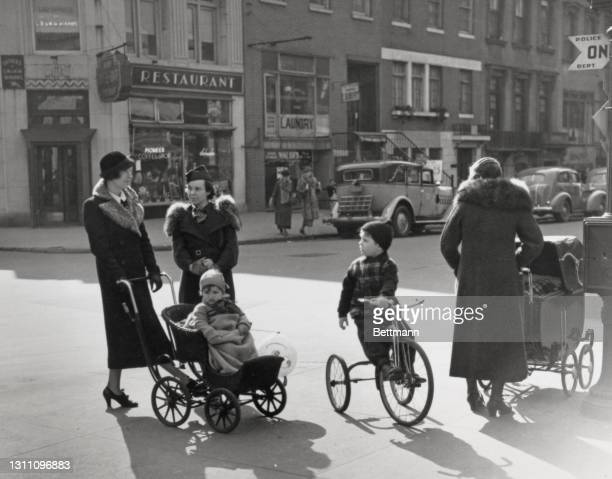 Mothers with a pushchair and a pram, and young child riding a tricycle on an early Spring scene on an unspecified street in the borough of Brooklyn,...