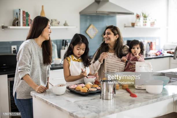 2 mothers with children makings cupcakes in kitchen - family stock pictures, royalty-free photos & images