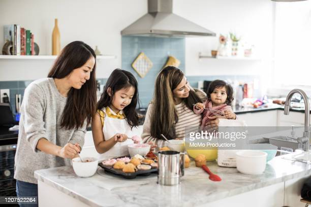 2 mothers with children makings cupcakes in kitchen - black hair stock pictures, royalty-free photos & images