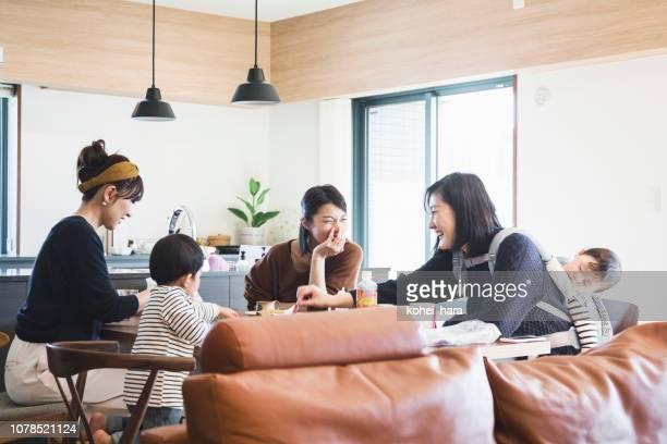 テーブルで話している子供を持つ母親 - 親睦会 ストックフォトと画像