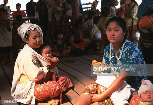 Mothers with their children wait outside a clinic in a Karen refugee camp north of the Thai town, Mae Sot. Camps in this area are filled with Burmese...