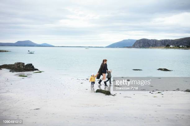 mothre walking with daughters on sandy norwegian beach - innocence stock pictures, royalty-free photos & images