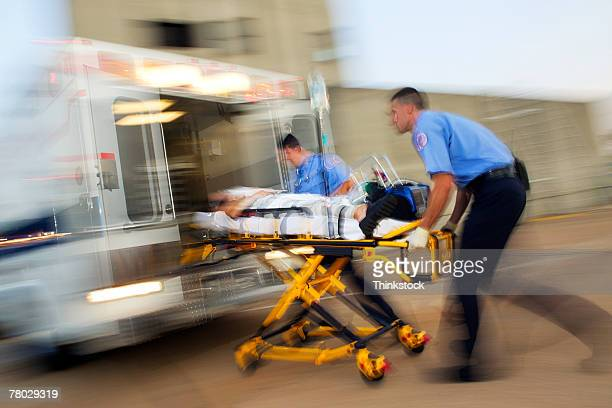 Motion blur image of two medics loading a patient on a stretcher into the back of an ambulance