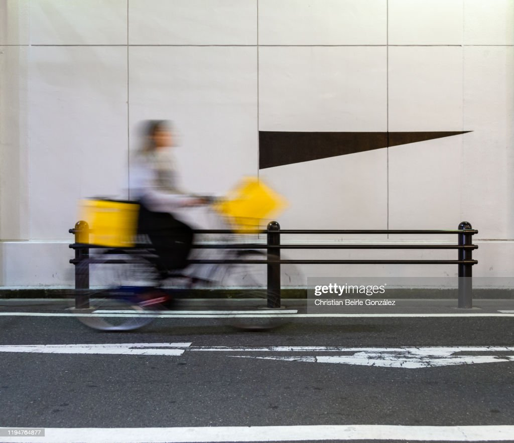 Motion blur of a female cyclist on street in Osaka, Japan : Stock-Foto