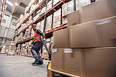 Motion blur of a man moving boxes in a warehouse