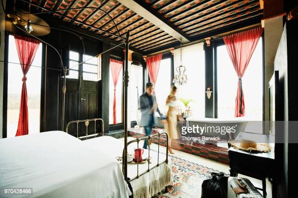 Motion blur of couple handing hands and walking through bedroom of boutique hotel