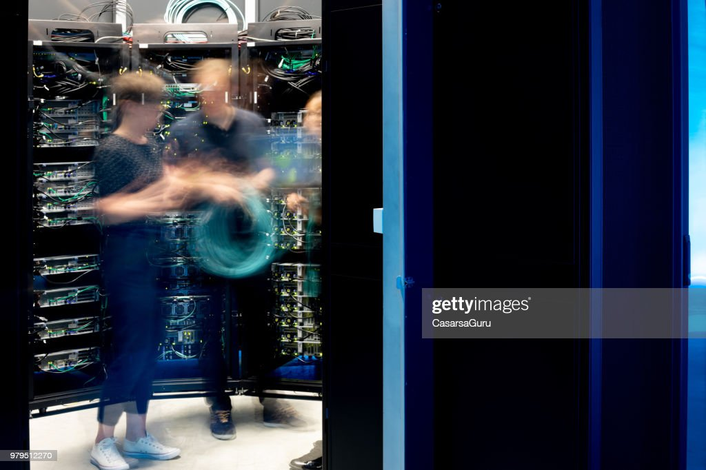 Motion Blur of Group of IT Engineers in Server Room : Stock Photo