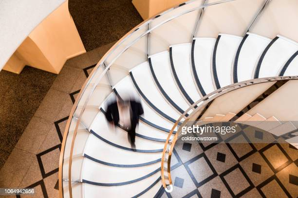 motion blur of speeding businessman on abstract spiral staircase - architectural feature stock pictures, royalty-free photos & images