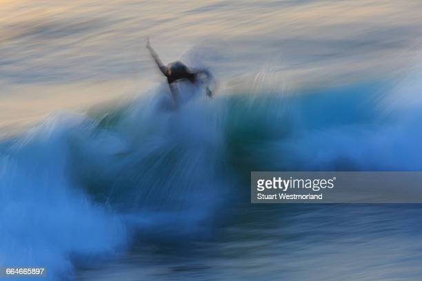 Motion blur of surfer surfing wave patterns after sunset, Pacific Beach, San Diego, CA, USA