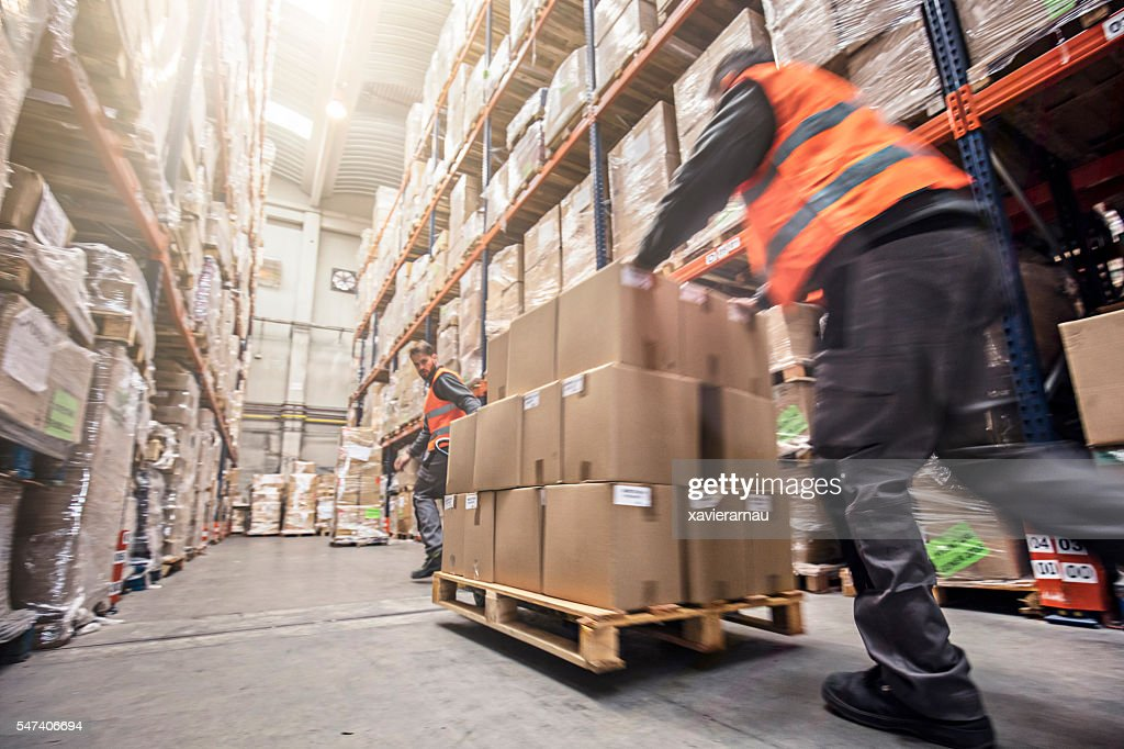 Motion blur of two men moving boxes in a warehouse : Stock Photo