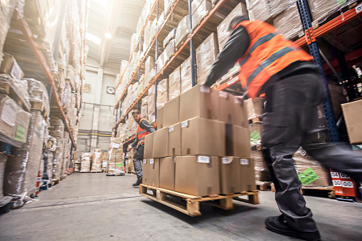 Motion blur of two men moving boxes in a warehouse 547406694