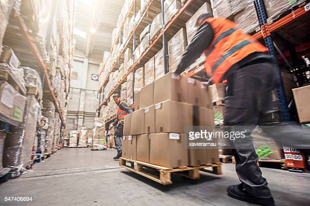 motion blur of two men moving boxes in a warehouse - vervoer stockfoto's en -beelden