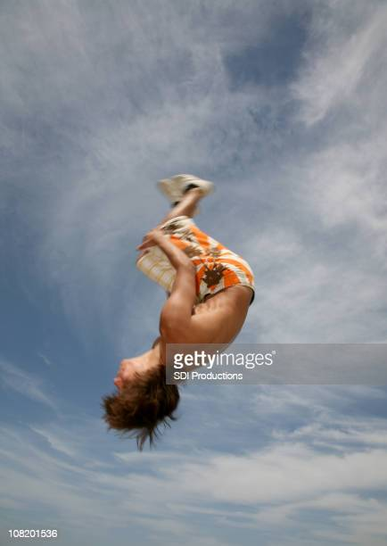 Motion Blur of Young Man Flipping Upside in Air