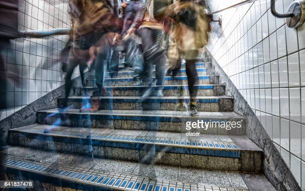 Motion blurred commuter in subway station stairs