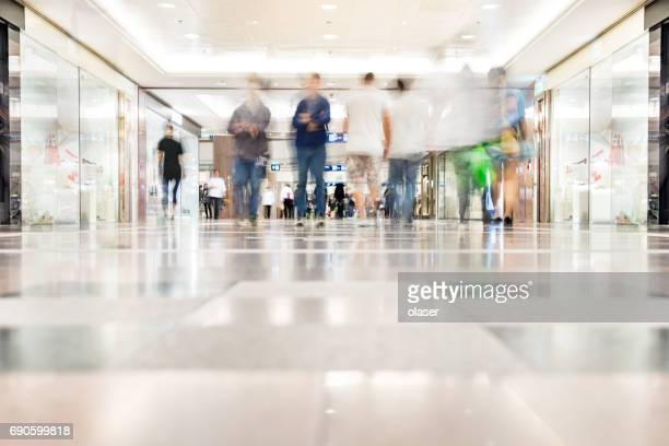 motion blurred customers walking in shopping mall, hong kong - shopping mall stock pictures, royalty-free photos & images