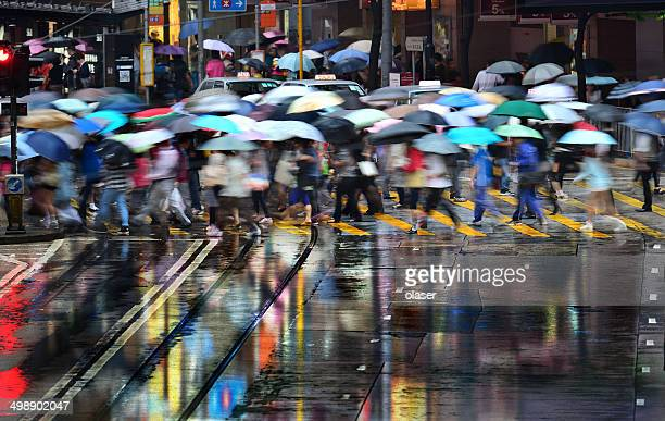 Motion blurred pedestrians crossing Hong Kong street in the rain