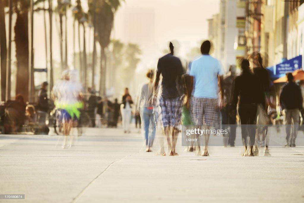 Motion blurred pedestrians on boardwalk : Stock Photo