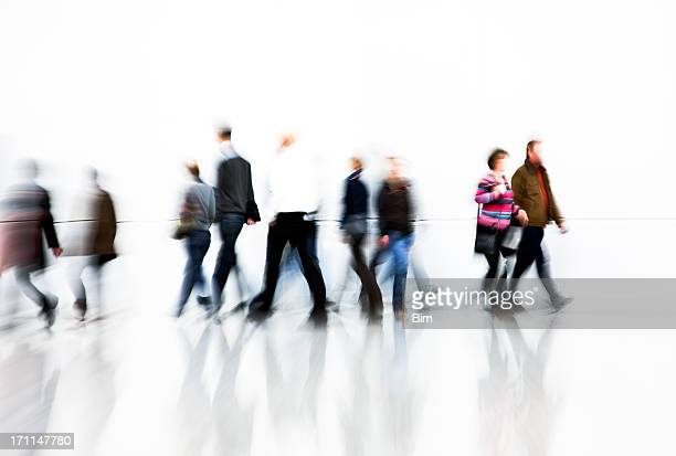 Motion Blurred Pedestrians Rushing In Front Of White Wall