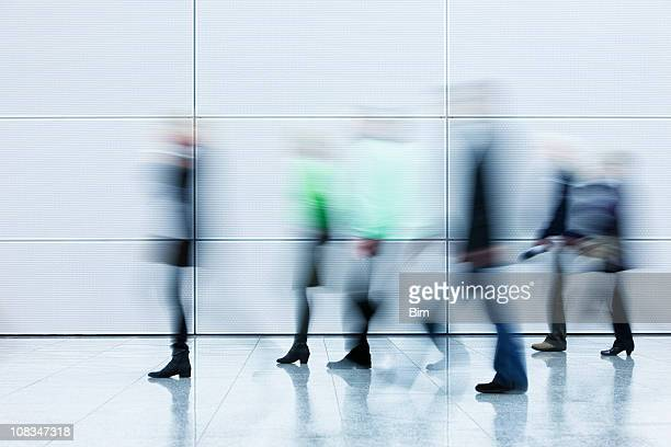 motion blurred pedestrians walking in white hallway - female streaking stock pictures, royalty-free photos & images