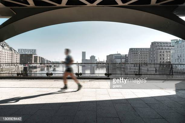 motion blurred person running on oberbaumbrücke in berlin - berlin stock pictures, royalty-free photos & images