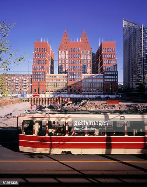 motion blurred red tram passing construction site. - la haye photos et images de collection
