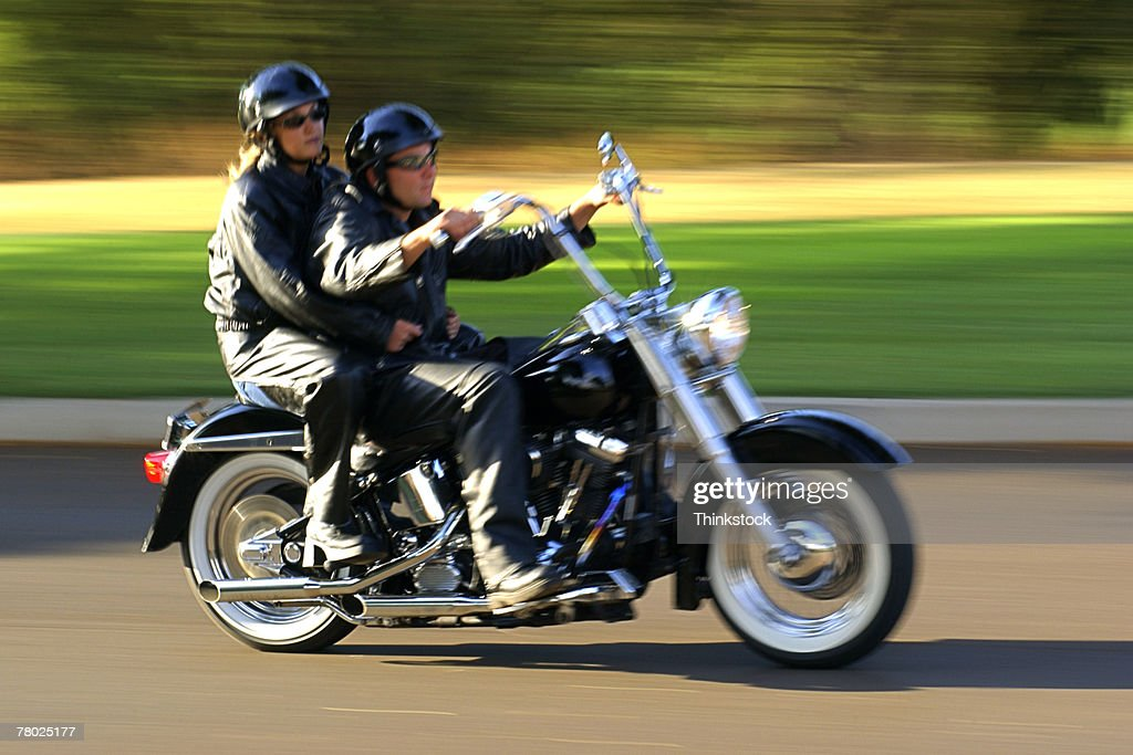Motion blurred shot of a couple riding fast past the viewer on a motorcycle. : Stock Photo