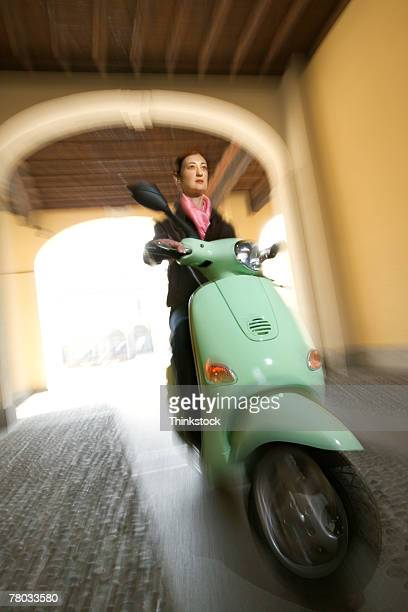 Motion blurred shot of a woman driving her scooter through a small arched tunnel toward the viewer.