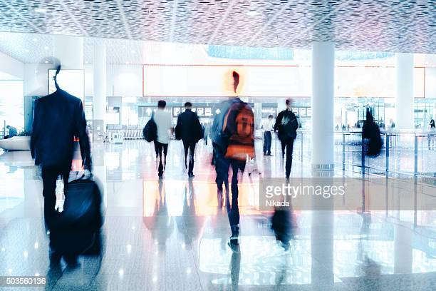 motion blurred travellers walking in modern airport hallway