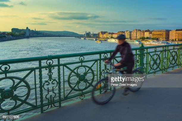 motion blurred unrecognizable cyclist on the liberty bridge in budapest, hungary - danube river stock pictures, royalty-free photos & images