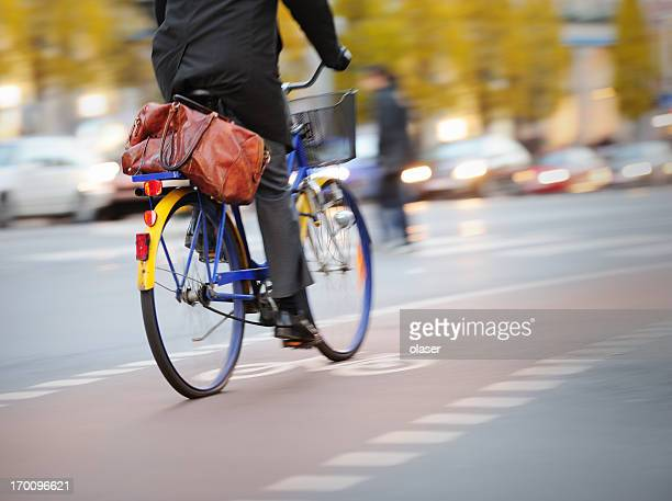 Motion blurred young adult businessman in bike lane and traffic