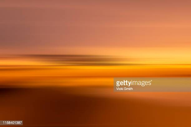 motion effect of a vibrant colored sunrise over the ocean - focus on background stock pictures, royalty-free photos & images