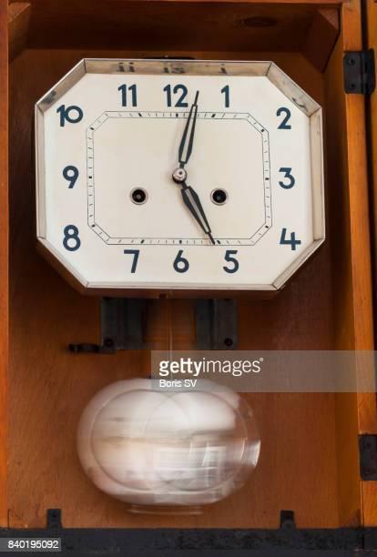 Motion of time. Swinging pendulum of retro clock on the wall