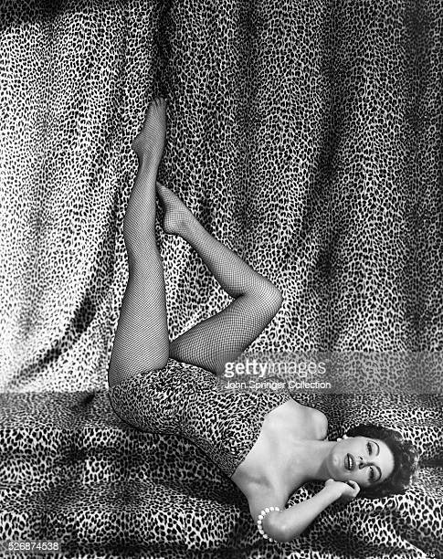 Motion picture actress Ava Gardner poses in a leopard skin outfit with matching backdrop