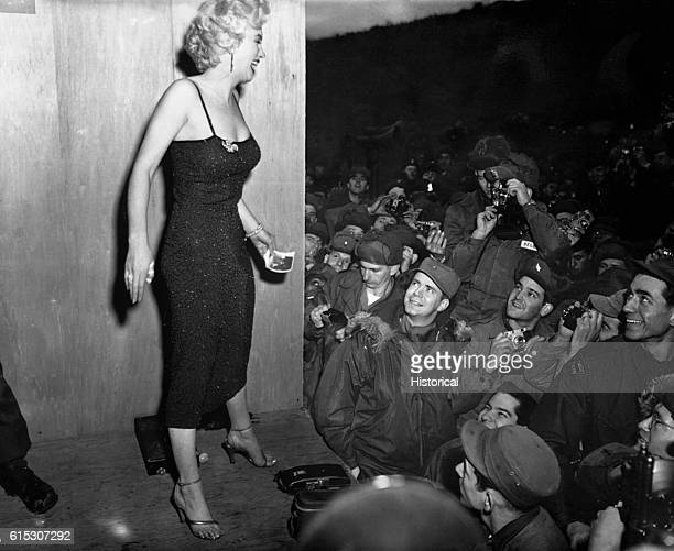 """Motion picture actress, Marilyn Monroe, appearing with the USO Camp Show """"Anything Goes."""" Here, she poses for the shutterbugs after a performance at..."""