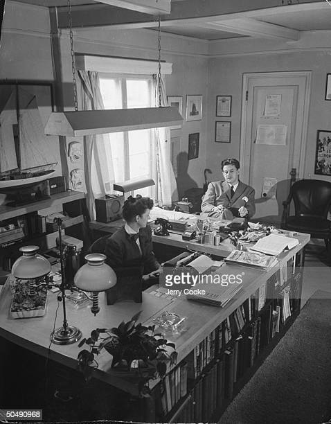 Motion picture executive Preston Sturges talking to his secretary in his office at California Studios
