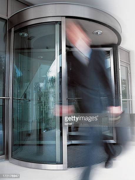 Motion-blurred businessman exiting building's rotating doors