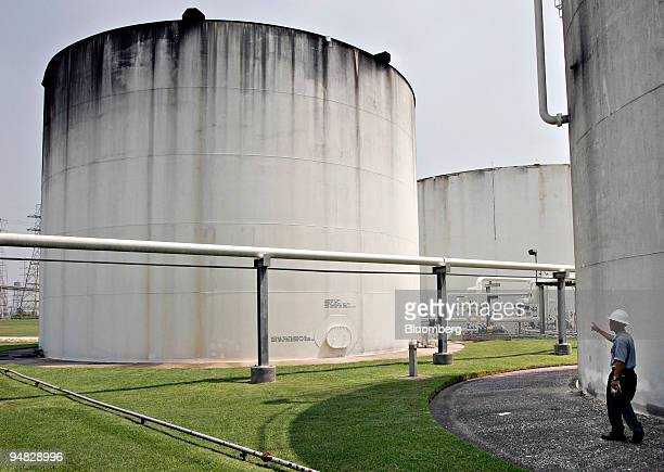 Motiva terminal operator Mustapha Bouchenni right points toward a large storage tank where ethanol is stored after being pumped and mixed with...