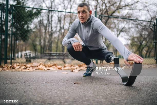 motivated amputee athlete stretching before running - amputee stock pictures, royalty-free photos & images