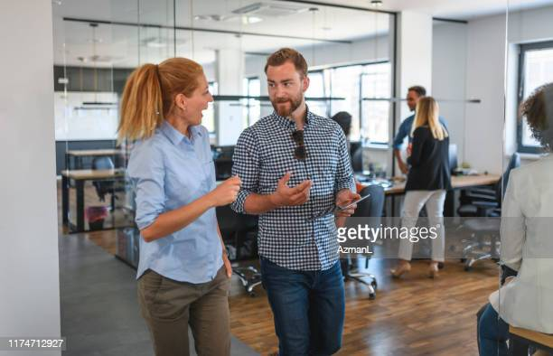 motivated businesspeople walking and talking through office - medium group of people stock pictures, royalty-free photos & images